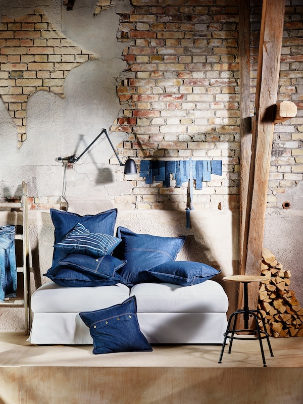 A lot of cushions in blue SISSIL cushion covers lie on top of two footstools against a wall in a run-down building.