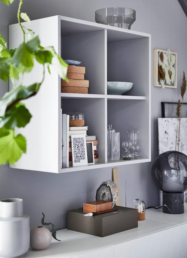 Uma estante HAVSTA em branco com livros, cestos e floreiras, ao lado de um módulo de arrumação em branco com as portas fechadas.