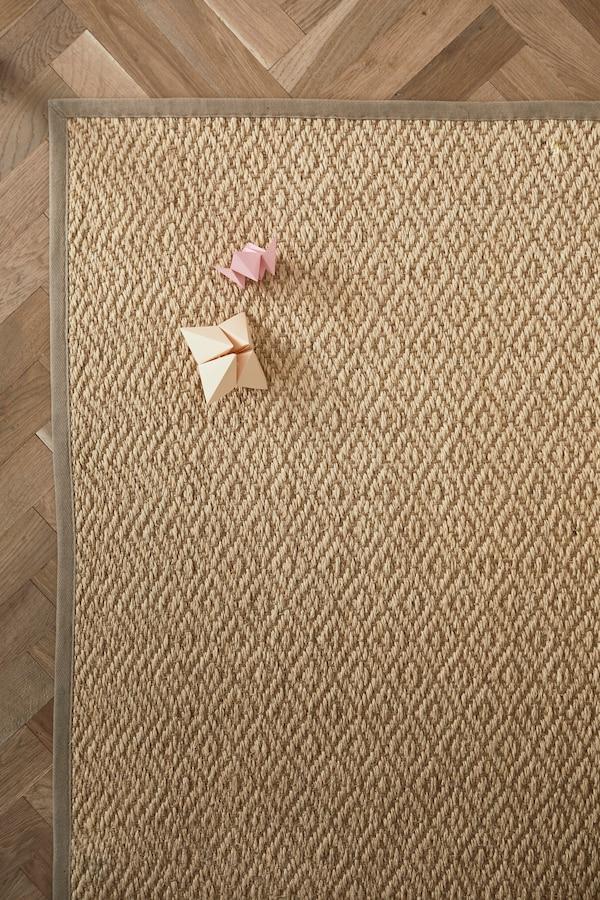 Et flatvevd naturfarget VISTOFT teppe ligger på et gulv.