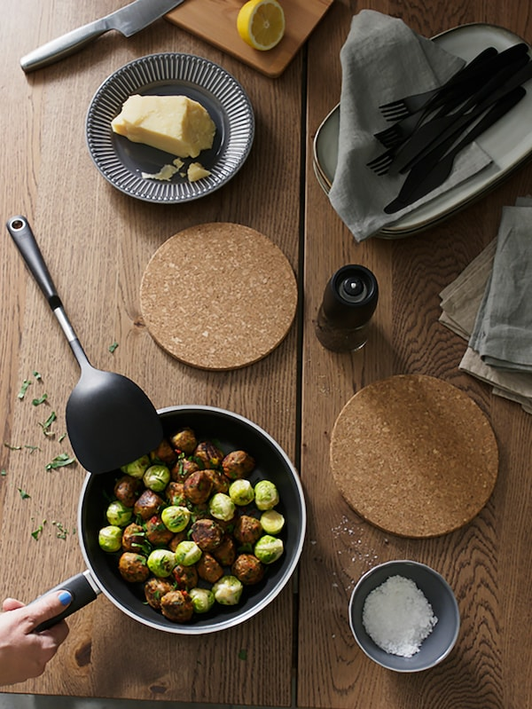 Two HEAT cork pot stand on a table with KAVALKAD frying pan. IKEA 365+ HJÄLTE use as wok turner for the meatballs on the KAVALKAD frying pan.