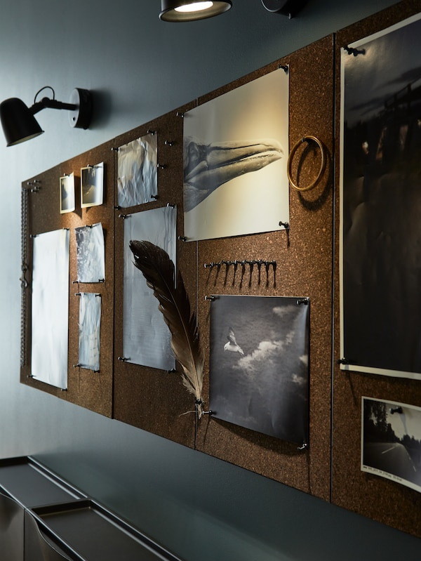 Corkboards with black and white pictures of birds, a feather, a golden bracelet and black wall lamps.