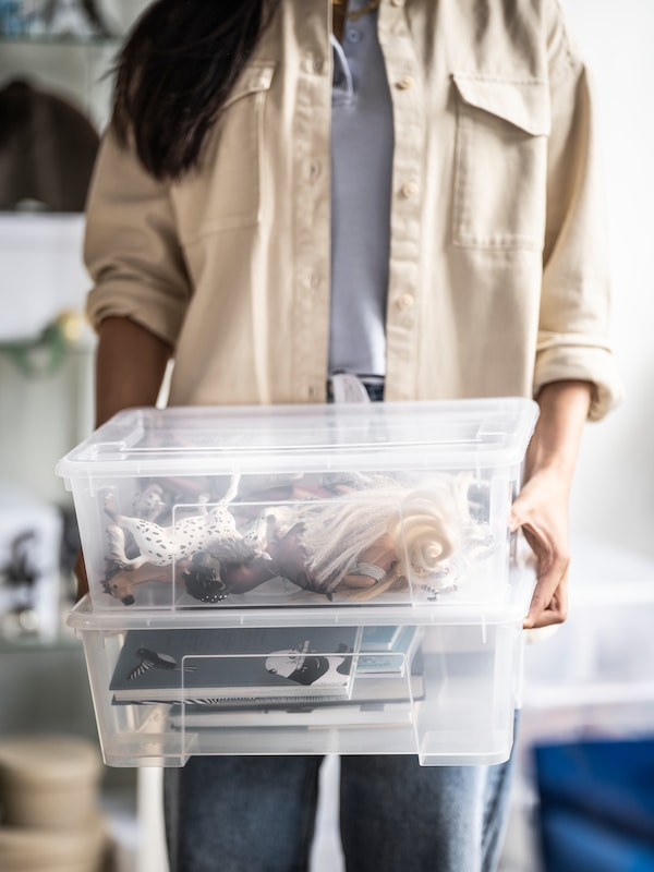 A woman stands and holds two transparent SAMLA boxes, one on top of the other, which contain toys, books and other items.