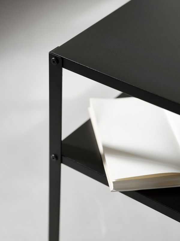 The corner of a black KNARREVIK side table showing the top surface and the shelf below as well as the joint detail.