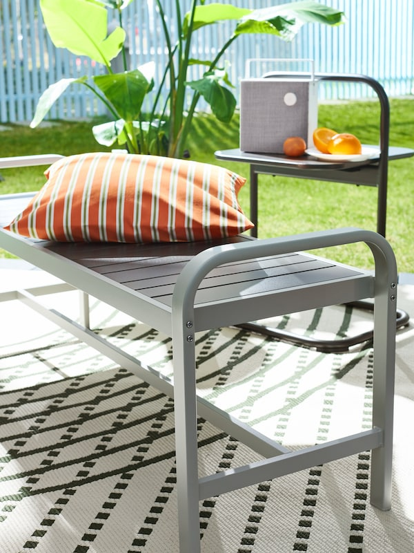 A sunny backyard with a cushion lying on a SJÄLLAND outdoor bench beside a HUSARÖ side table with a Bluetooth speaker on top.