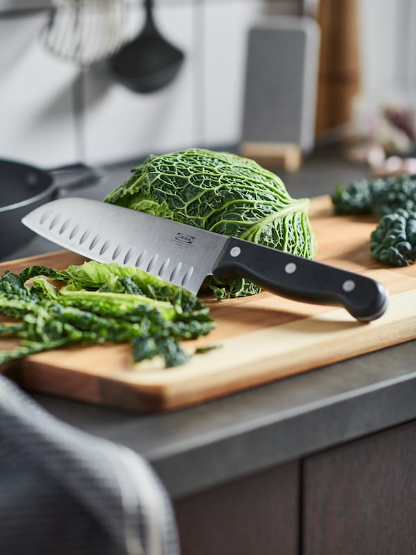 A kitchen worktop with chopped-up savoy cabbage and a VARDAGEN knife on a SMÅÄTA chopping board.