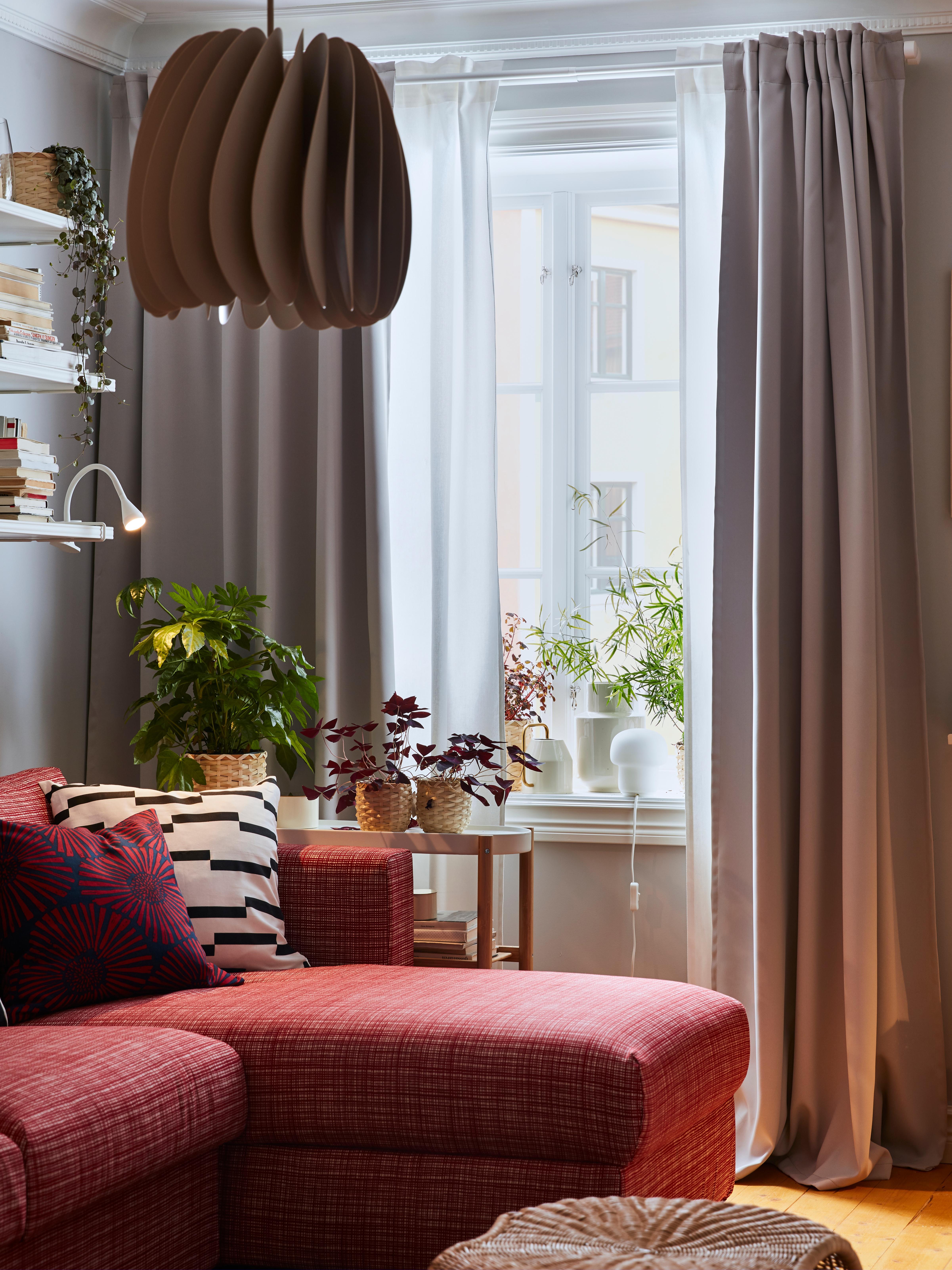 Lampada a sospensione, divano rosso e finestra con tende semioscuranti MAJGULL grigio chiaro sovrapposte a tende bianche.