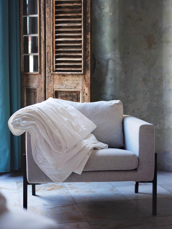 Een grijze stoel met een wit dekbed gedrapeerd over één armleuning staat tegen een rustieke, houten deur op een tegelvloer.