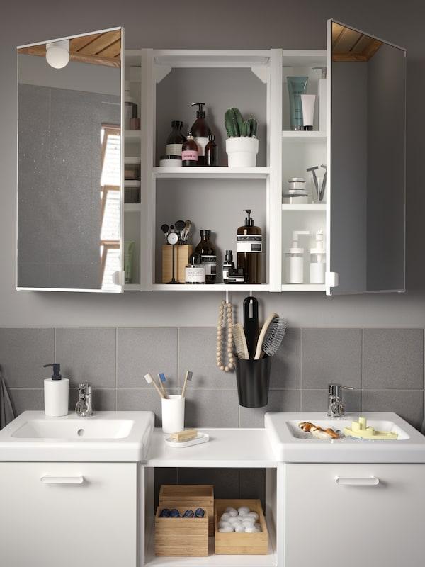 Baño con azulexos grises, un conxunto de lavabos e mobles de soporte en branco e un armario de parede con dúas portas de espello.