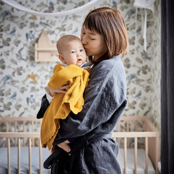 O mămică stă în fața unui pătuț, în dormitor, și ține în brațe bebelușul învelit într-o pătură SOLGUL galben închis.