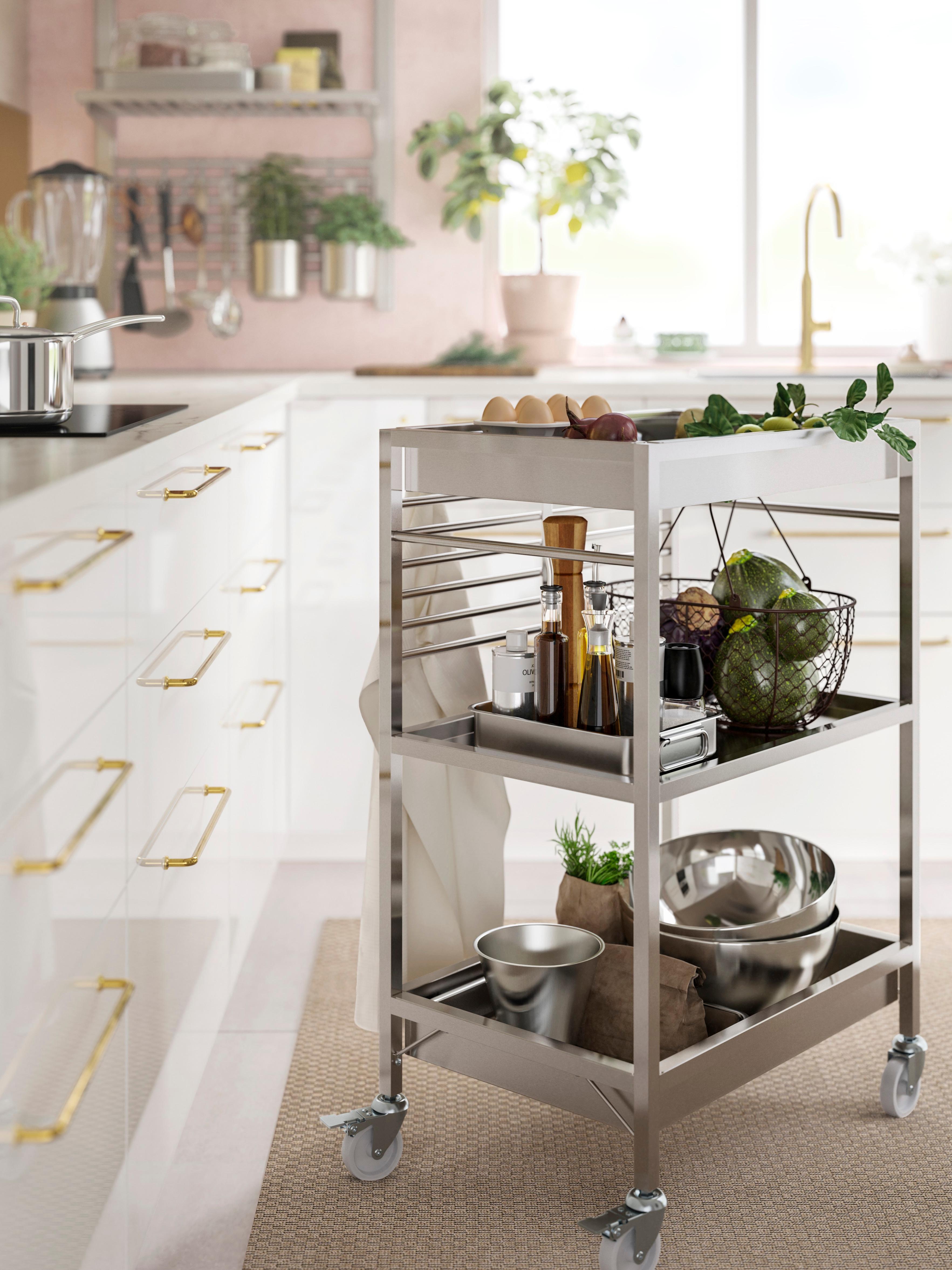 Carrinho de cozinha KUNGSFORS em aço inoxidável com prateleiras, calhas e rodízios com travão, com tigelas e alimentos, ao lado de armários de cozinha.