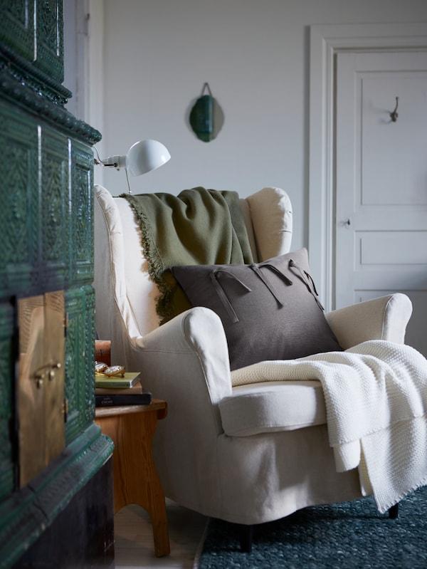 Un cojín con funda AINA en gris sobre un sillón orejero STRANDMON junto a unas cuantas mantas suaves.