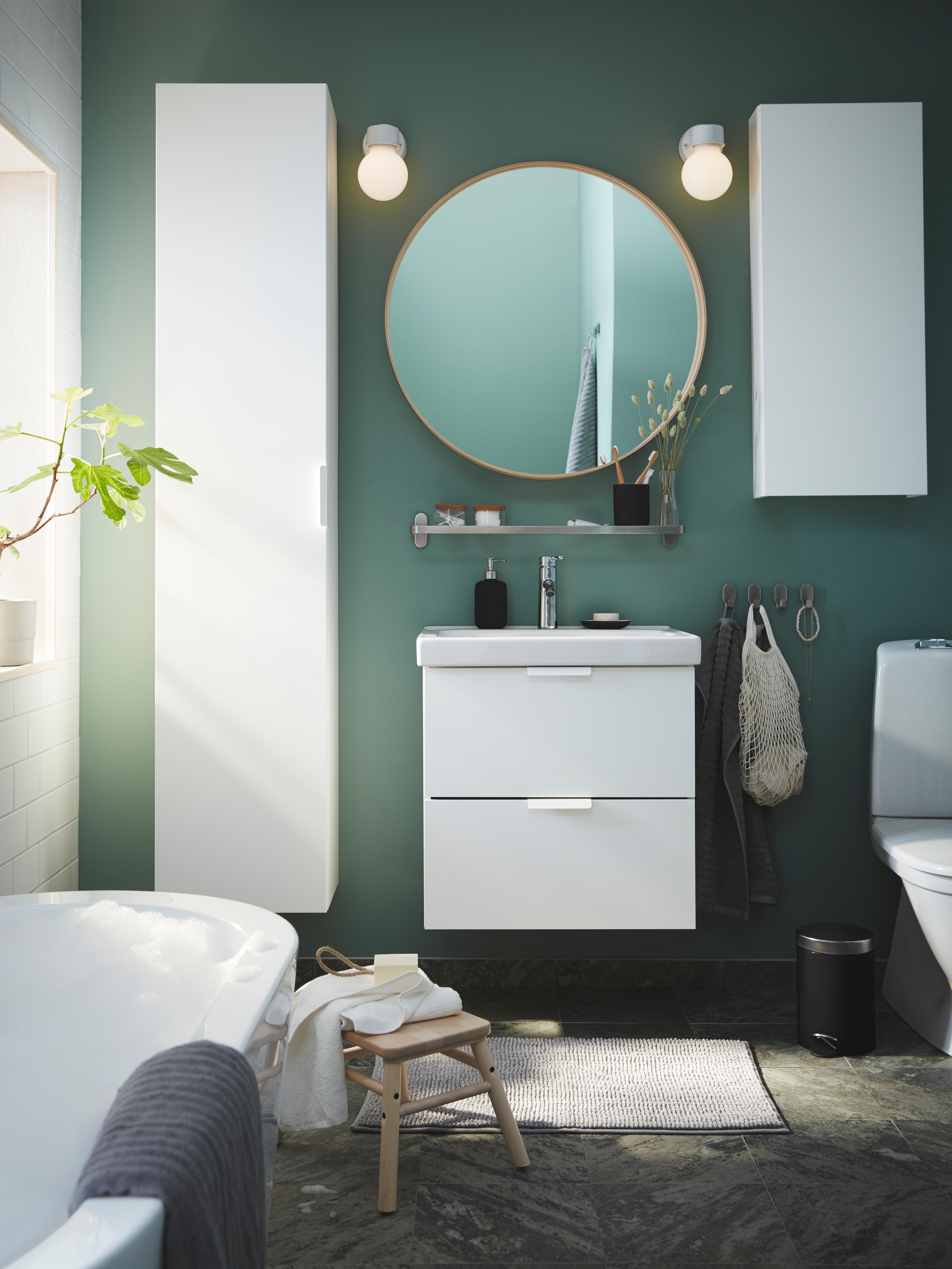 Specchio STOCKHOLM rotondo, in impiallacciatura di frassino, sulla parete verde di un bagno, sopra a un mobile per lavabo bianco e in mezzo a due mobili coordinati - IKEA