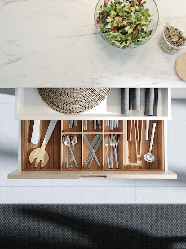 Åben køkkenskuffe med bestikskuffe af bambus. Bestik og forskellige køkkenredskaber er pænt organiseret i en bestikbakke.