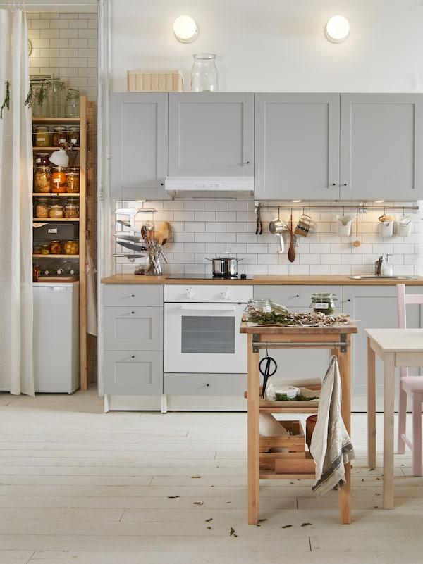 Una cocina con armarios de pared y armarios bajos en gris claro, un horno blanco y una estantería con diversos productos.