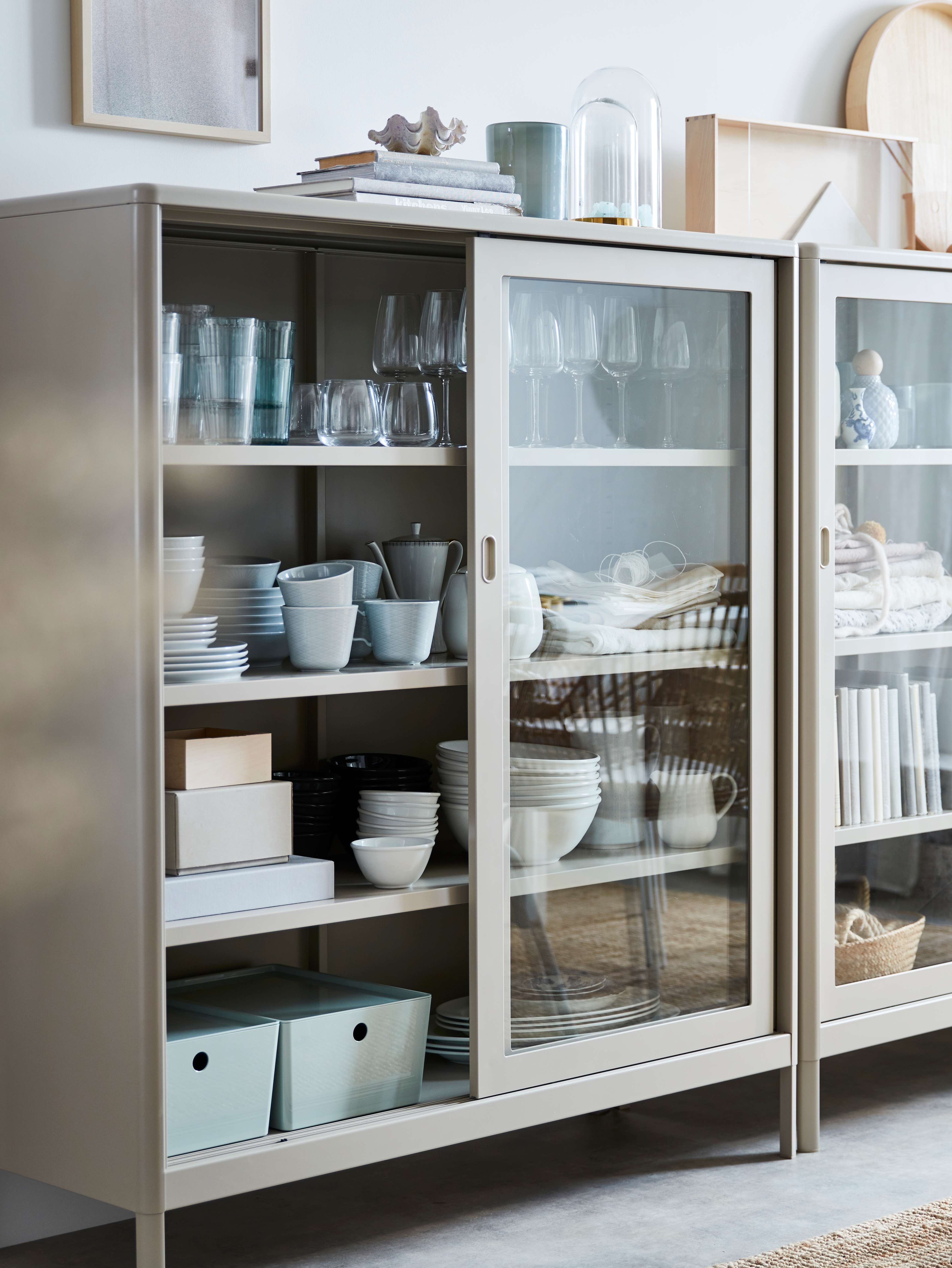 A beige IDÅSEN cabinet with sliding glass doors holds glasses, tableware and storage boxes, with books and decor on the top.
