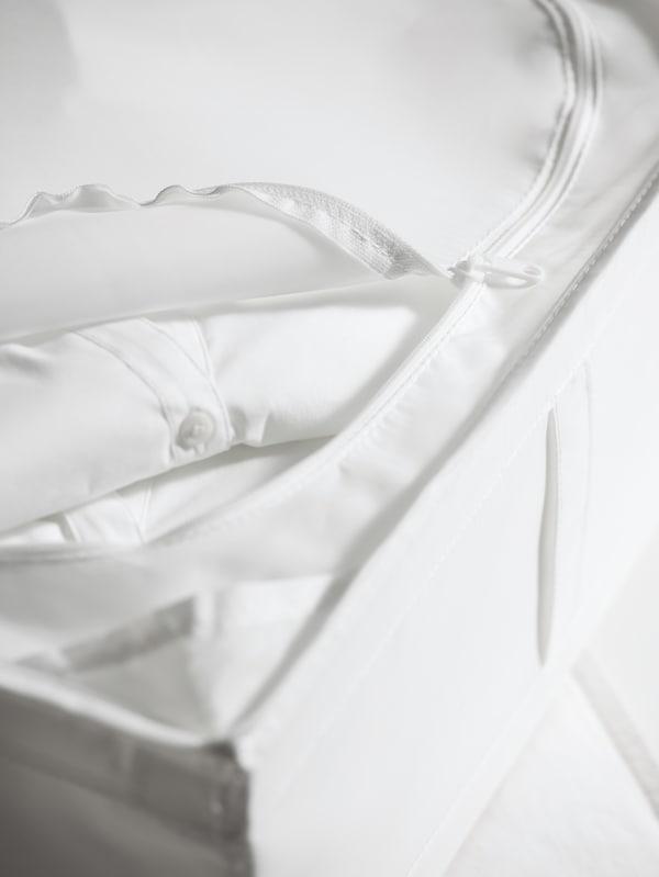 Överdelen på en SKUBB förvaringslåda med dragkedjan delvis öppen, som visar att den är fylld med vikta vita kläder.