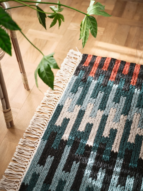 A light wooden floor with a flatwoven RESENSTAD rug in different shades of blue, gray and red and a plant in a plant stand.