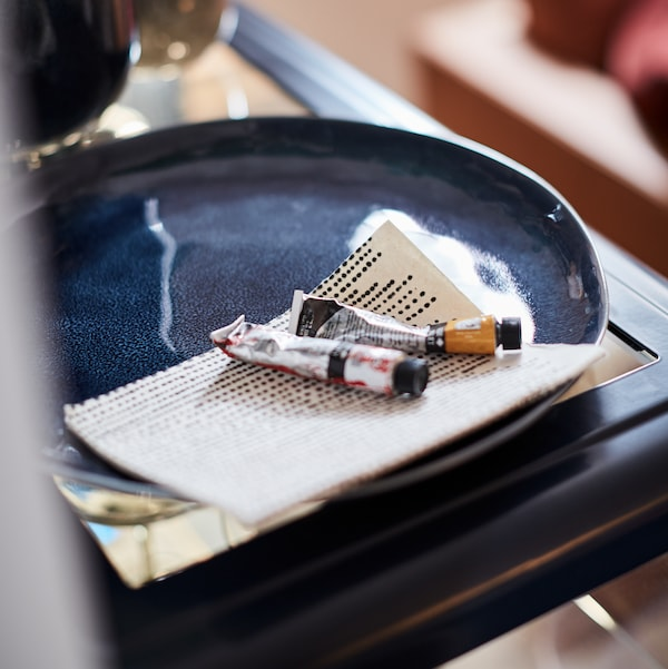 A close-up of two watercolour paint tubes and a piece of paper lying in an ERTAPPAD dish in blue on a table corner.