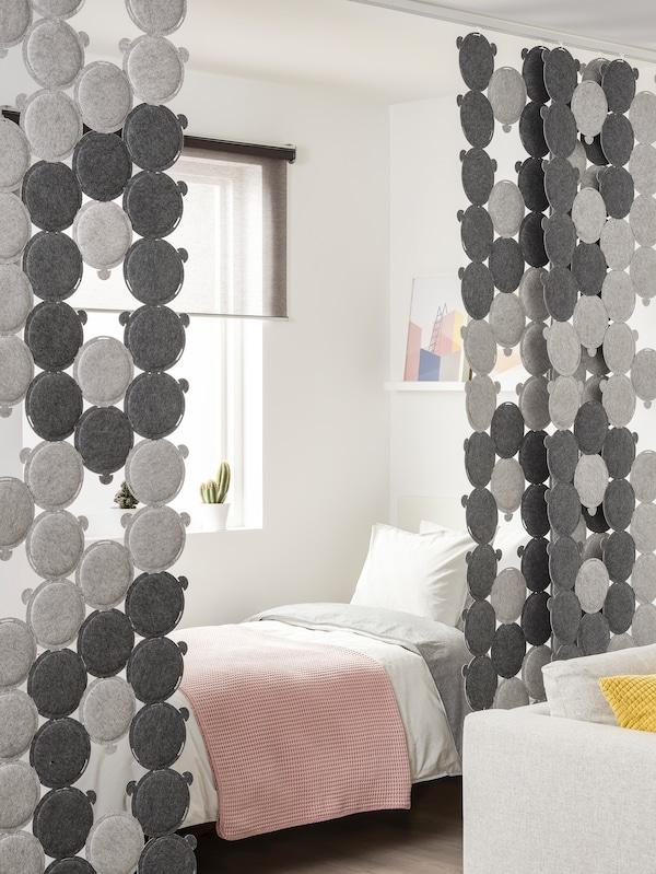 Un lit avec un couvre-lit rose est placé dans un coin derrière un rideau partiellement ouvert fait de panneaux acoustiques ODDLAUG.