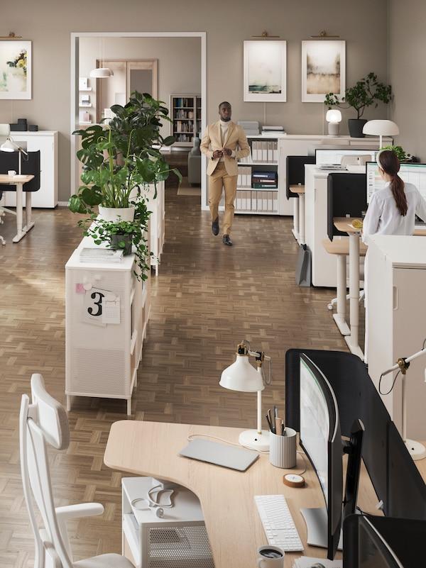 Ein Mann läuft durch einen Bürobereich mit Schreibtischen, auf denen Leuchten und Trennwände zu sehen sind, u. a. mit Stühlen, Aufbewahrungen, Grünpflanzen und Bildern.