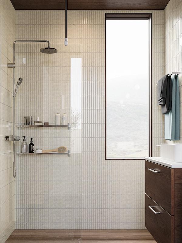 Koupelna s bílými obklady se dvěma policemi z nerezavějící oceli a sprchovou sadou BROGRUND. A věšák na ručníky se dvěma ručníky.