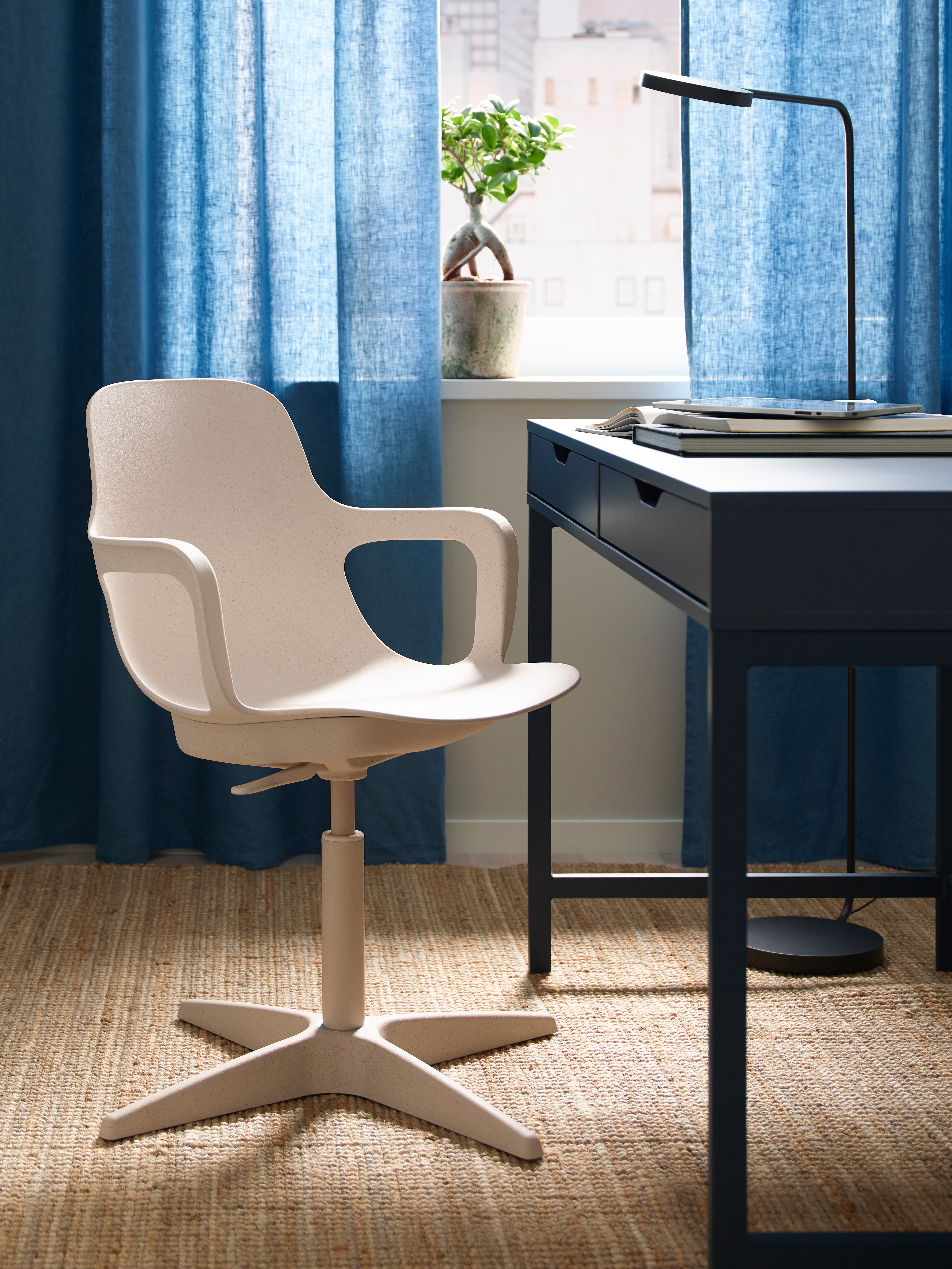 A white/beige ODGER swivel chair is on a jute rug by a blue desk, in front of a curtained window. The desk has books on it.