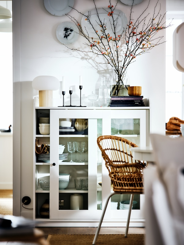 A white HAUGA cabinet with bi-fold glass doors in a white country-style room filled with objects, by a NILSOVE armchair.