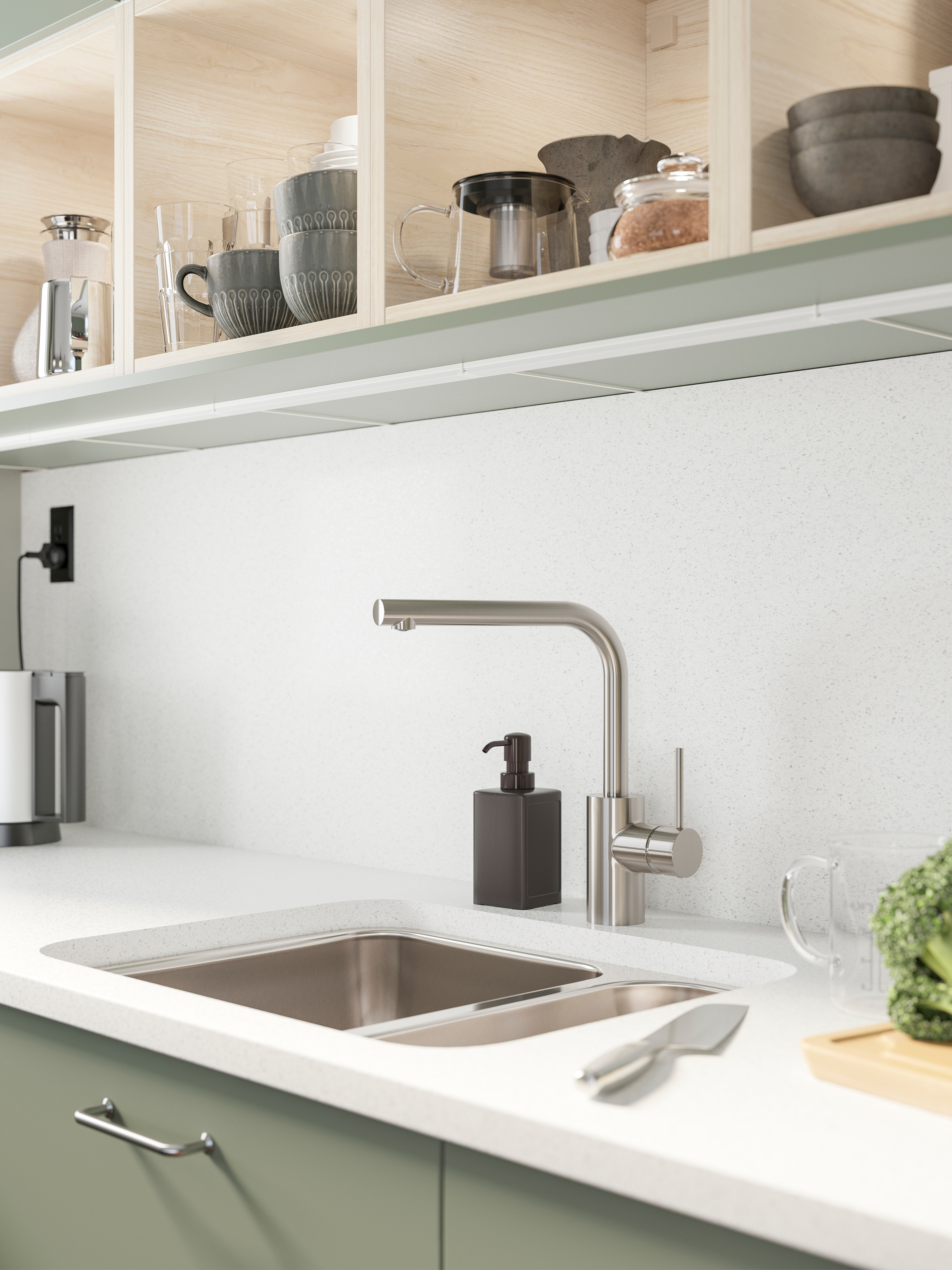 TÄMNAREN kitchen mixer tap, over a stainless-steel kitchen sink on a white countertop, and kitchen items in open cabinets.