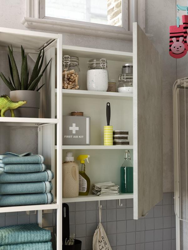Grunt skåp med öppen dörr som visar första hjälpen-set, tvättmedel i burkar, klädnypor och andra tvättartiklar.