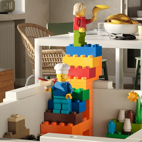 A white BYGGLEK box with a LEGO staircase climbing out of it holding two mini figures that have food in their hands.
