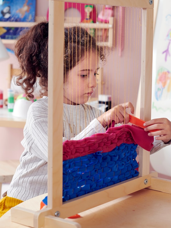 A child sitting at a table weaving with red and blue fabric on a LUSTIGT 7-piece weaving loom set.