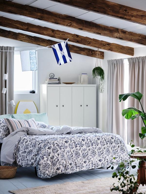 Un dormitorio con un ligero ambiente veraniego, una cómoda cama con funda nórdica JUNIMAGNOLIA, con estampado floral blanco / azul oscuro y 2 fundas de almohada.  Un armario IDANÄS blanco en el fondo de la habitación.