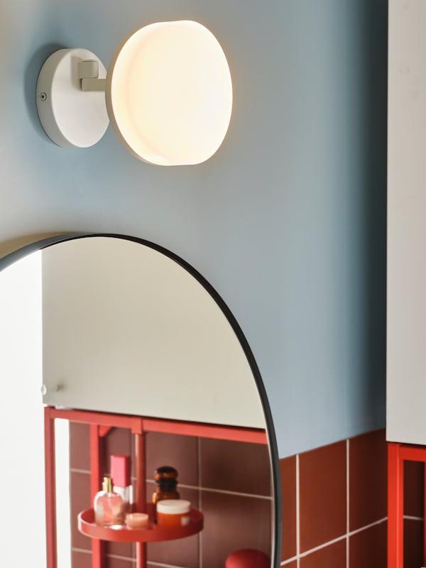 Lámpada de parede con brazo xiratorio montado sobre o espello redondo dun baño.