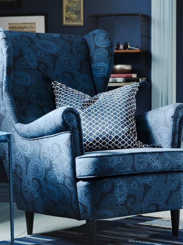سرير مع لحاف ووسادتين، عليهبياضات السرير PUDERVIVA ذات اللون الأزرق الداكن ووسائدأخرى.