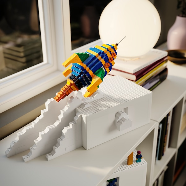 A rocket made from multicolour LEGO pieces set on a white BYGGLEK box that's near a lamp on a shelf by a window.
