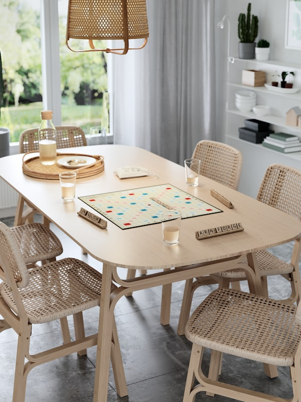 Spisebord og stoler av bambus og vevd papir, et brettspill, glass med saft og ei taklampe av bambus.