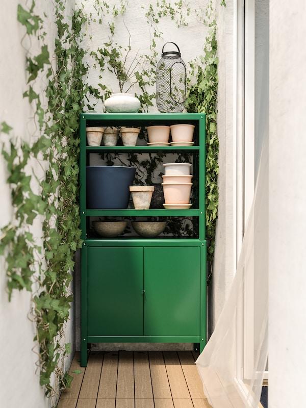 Ein grüner Schrank mit Übertöpfen auf Böden steht an einer weissen Wand mit Efeu.