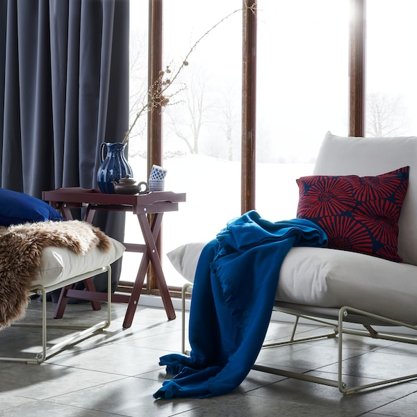 A white easy chair with a STJÄRNTULPAN cushion in dark blue and red and a blue POLARVIDE throw on it, near a large window.