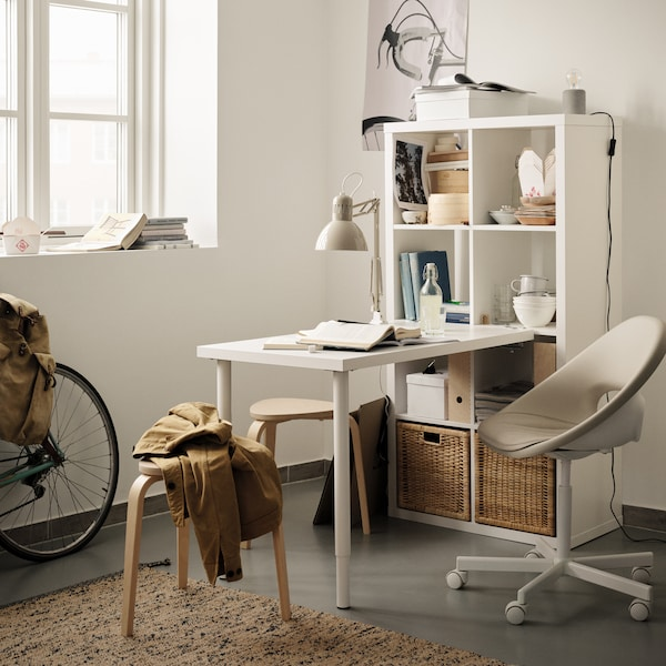 A KALLAX shelf in white standing against the wall with an adjoining table in the middle of a bright room.