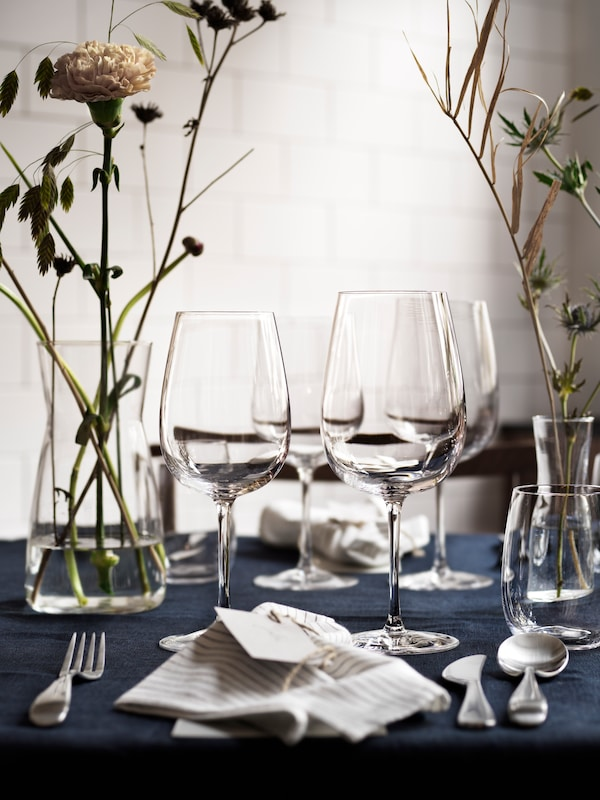 STORSINT red wine glasses and drinking glasses are gathered in the center of a set table next to a carafe used as a vase.