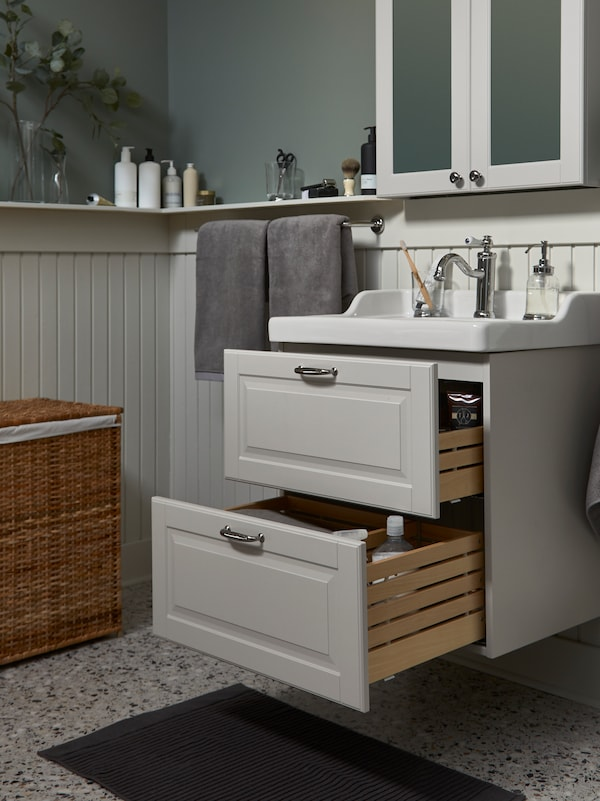 Meuble lavabo/lavabo GODMORGON/RÄTTVIKEN gris clair/blanc avec deux grands tiroirs ouverts et armoire à miroir au-dessus.