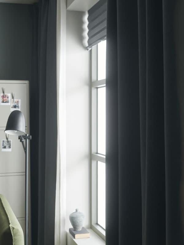 Das Licht scheint in ein Fenster mit hellgrauen Rollos, halbtransparenten Gardinen und dunkelgrauen abdunkelnden Gardinen.