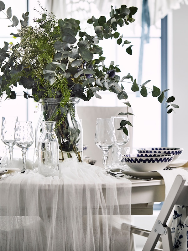 A wedding table with a large centerpeice of eucalyptus leaves
