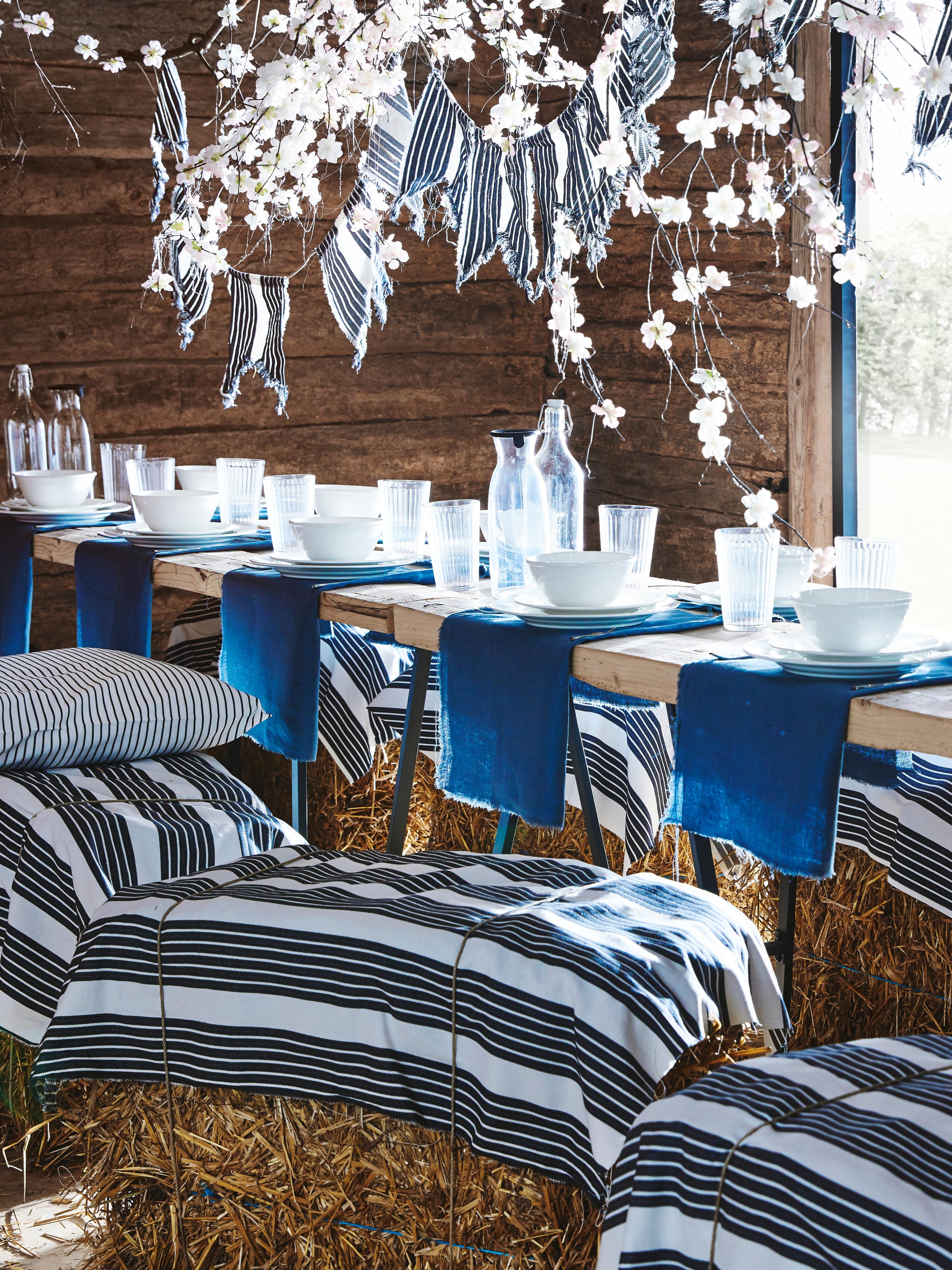 Izložbena postavka s dugim stolovima, balama sena i stolicama povrh kojih se nalazi METTALISE tkanina na belo-sive pruge.