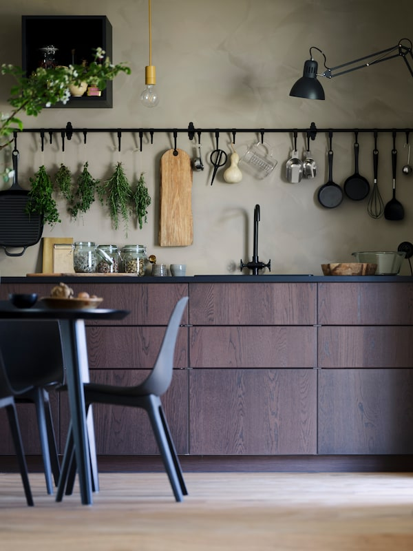 A brown SINARP kitchen with a beige wall. A black rail is mounted on the wall where kitchen utensils are displayed.