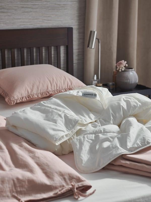 Una camera da letto e un letto IDANÄS, pronti ad accogliere la primavera con i piumini STJÄRNBRACKA e un set di copripiumini KRANSKRAGE rosa pallido.