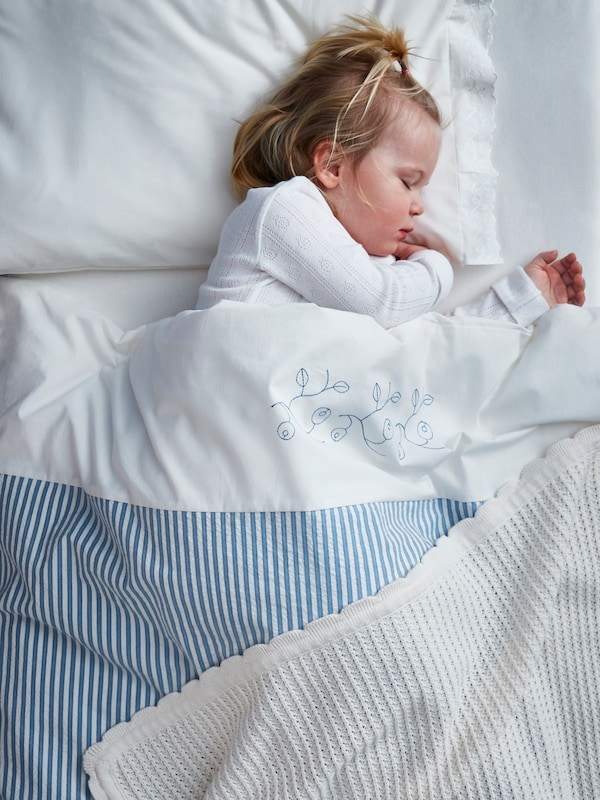 Unha meniña dorme nunha cama cun edredón e unha funda de almofada GULSPARV e unha manta branca da mesma serie.