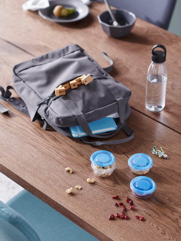 A grey STARTTID backpack, a filled IKEA 365+ water bottle and snack-filled PRUTA containers lying on a wooden tabletop.