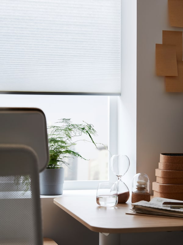 A HOPPVALS cellular blind, with a honeycomb structure, at a window, behind a work desk and chair.