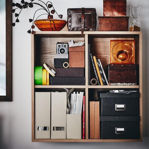 Élément mural EKET en plaqué chêne blanchi, rempli de dossiers et de boîtes de rangement.